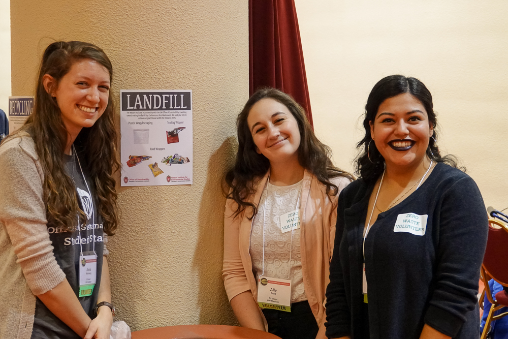Intern volunteers Anna Weinberg, Ally Burg, and Noemy Serrano (L-R) pose near a zero waste station in the exhibitor hall at Monona Terrace.