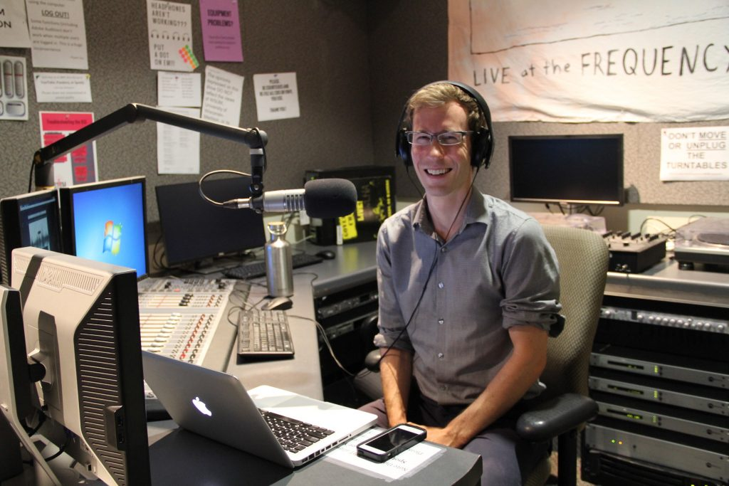 Green Fund Program Manager for the Office of Sustainability Ian Aley recording the podcast in the WSUM 91.7FM studio.